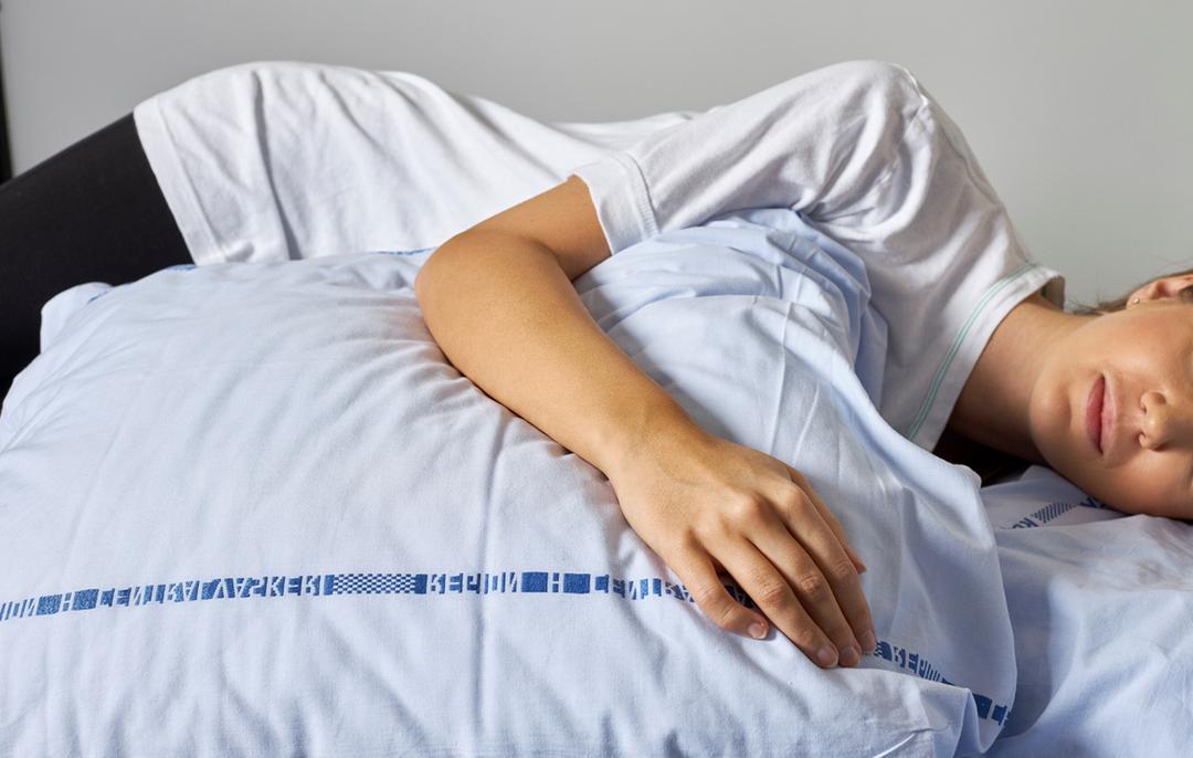 Foto af en patient, der ligger på siden og hviler sin arm på en pude.