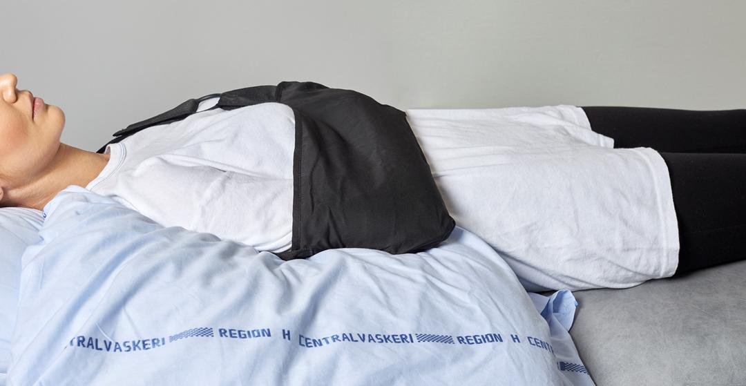 Foto af en patient, der ligger på ryggen med en pude under overarmen og armen på maven.
