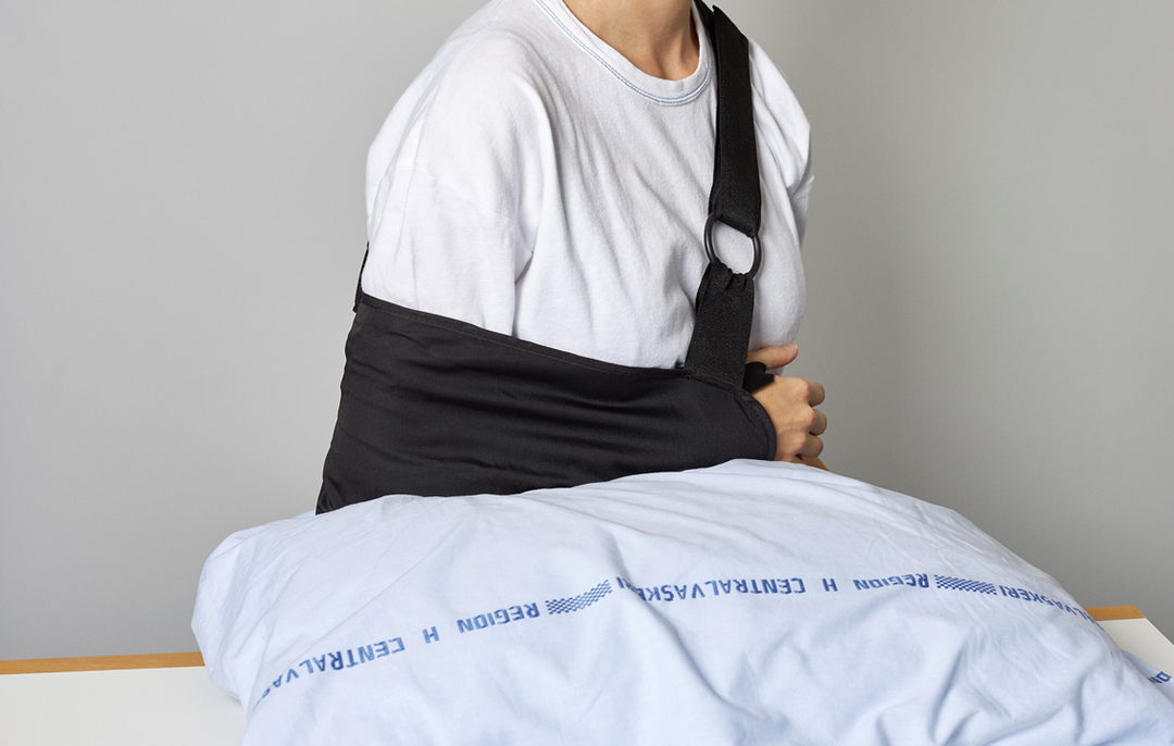 Foto af en patient, der sidder ned og hviler sin underarm på en pude foran sig.