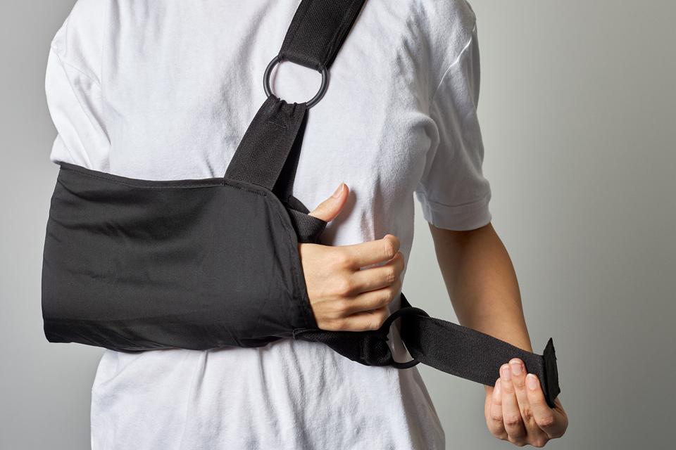 Foto af en patient, der spænder den nederste rem om bag ryggen.