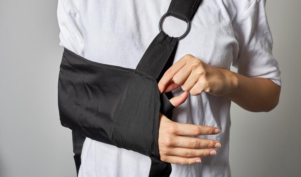 Foto af en patient, der sætter tommelfingeren ind i stroppen.