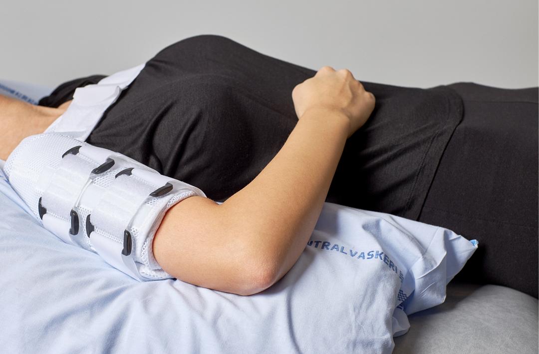 Foto af en person, der ligger på ryggen med en pude under overarmen og hånden på maven.
