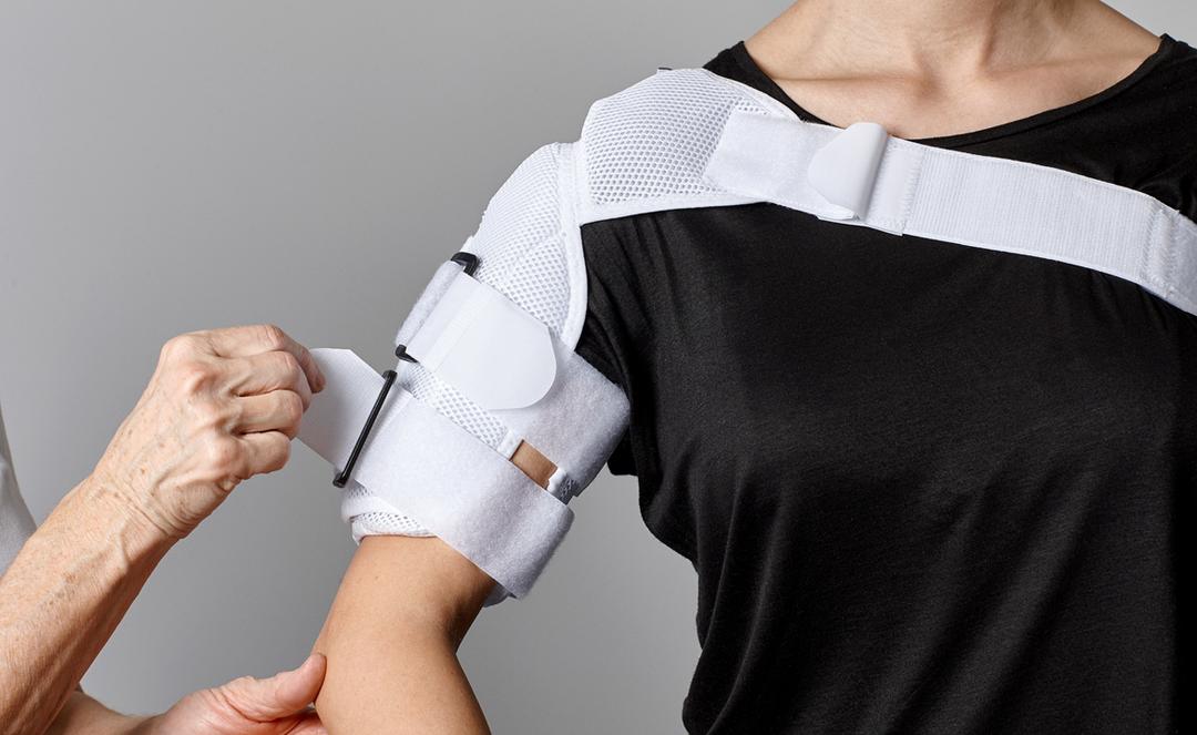 Foto af en person, der får spændt bandagen om armen.