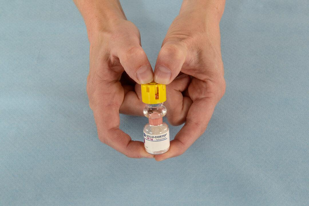 Billedet viser, hvordan man trykker plastikhætte på ampullen nedad.