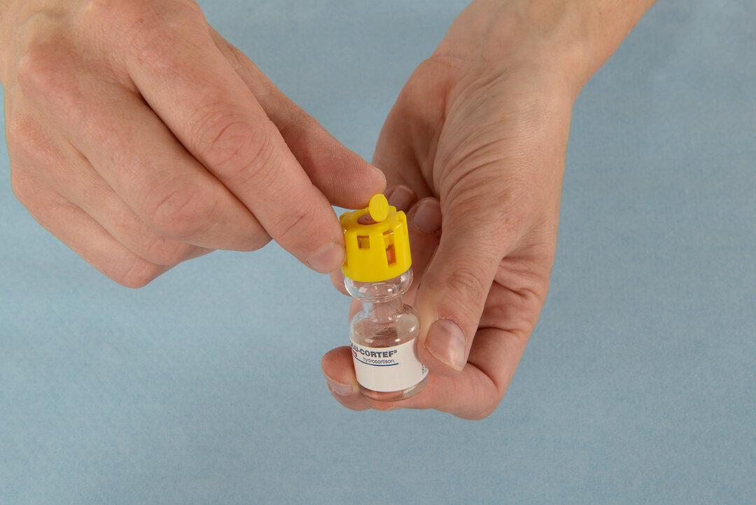 Billedet viser, hvordan man fjerner den runde plastikbeskyttelse på toppen af flasken.