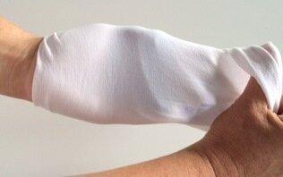 En hånd vender vrangen ud på strømpeskaftet og hælen af en strømpe.