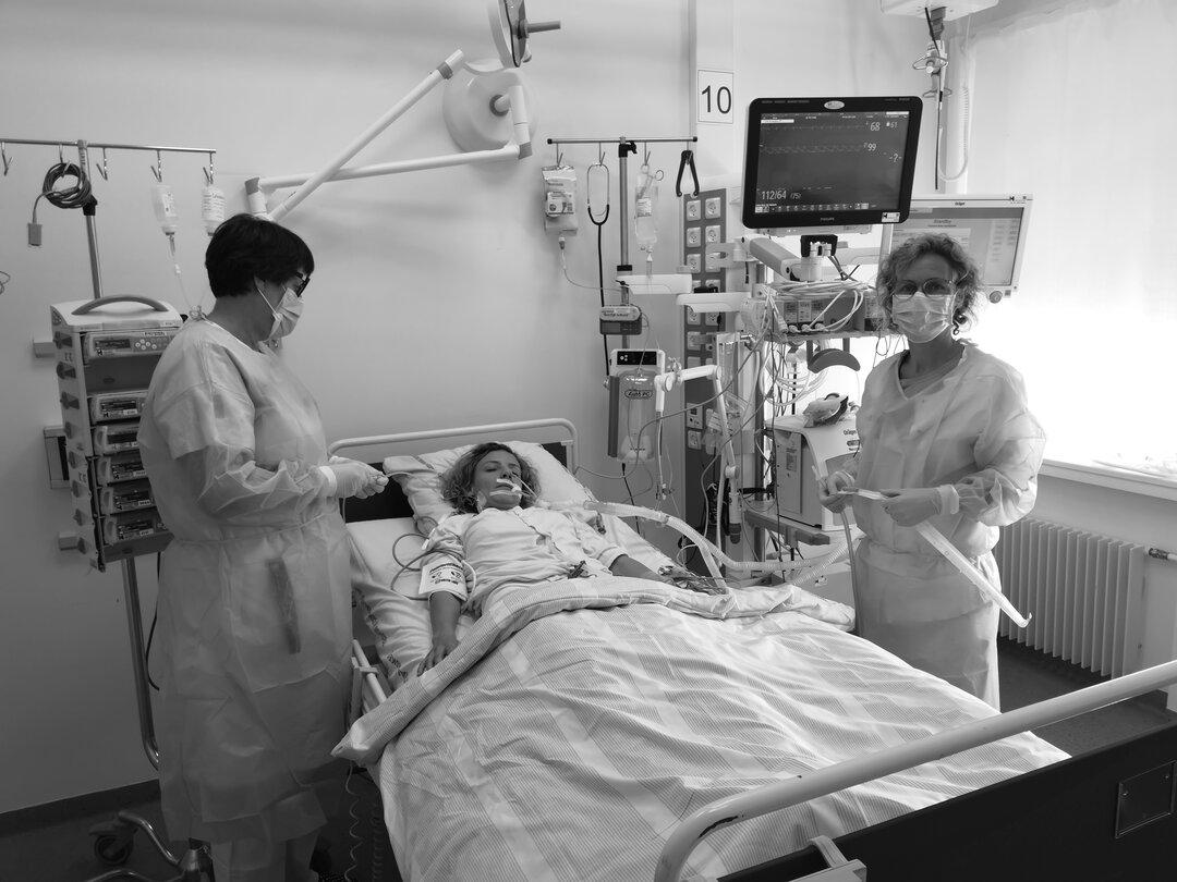 Patient ligger i seng, med en sygeplejerske på hver side af sengen.