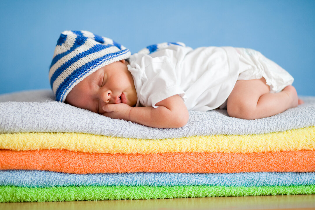Billede af en baby, der sover på håndklæder.