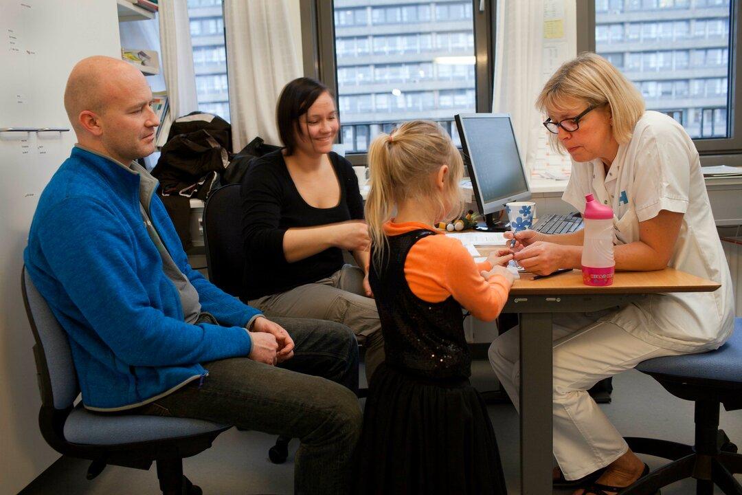 Patient og forældre i dialog med sygeplejerske