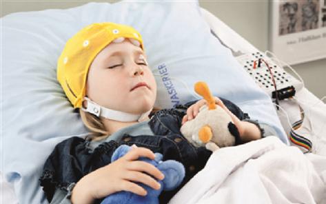 Sengeliggende patient med bamser, elektroder og hue