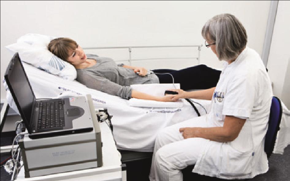 Sygeplejerske undersøger sengeliggende patient