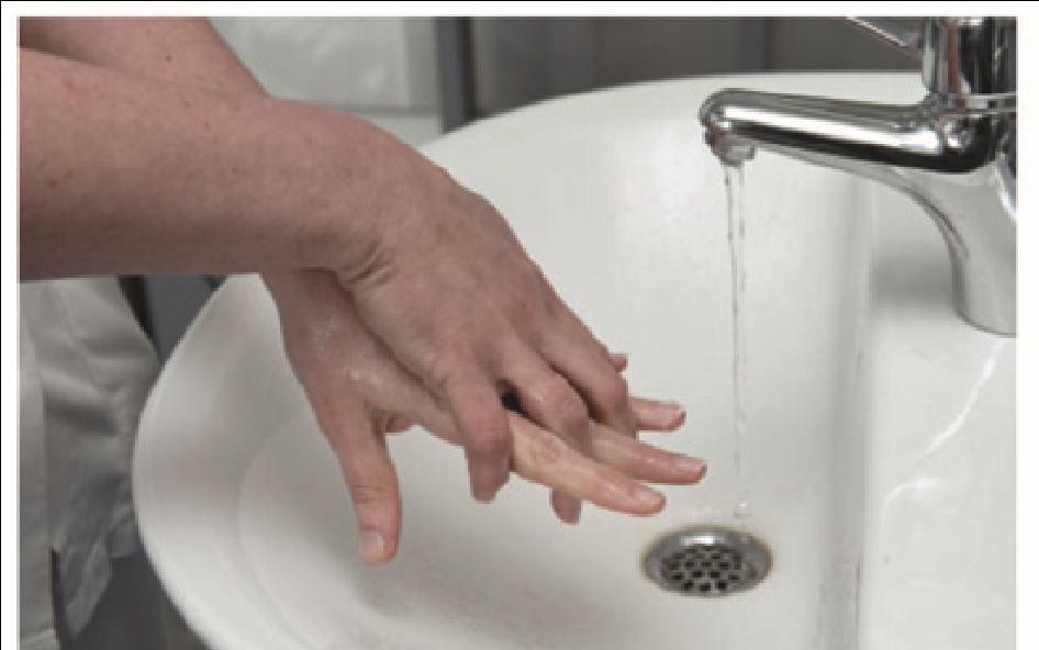 Sygeplejerske vasker området mellem fingrene på sine hænder