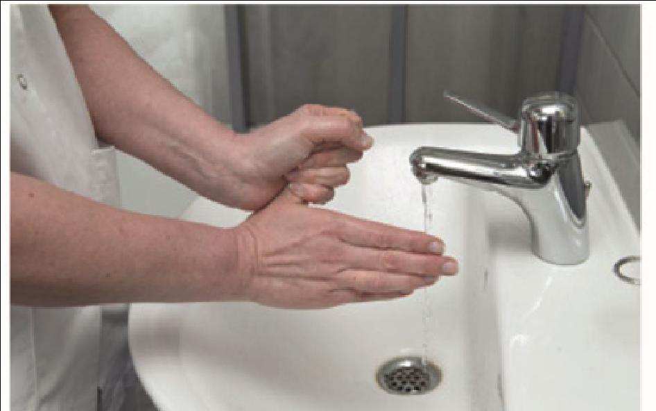 Sygeplejerske vasker sin ene tommelfinger med den anden hånd