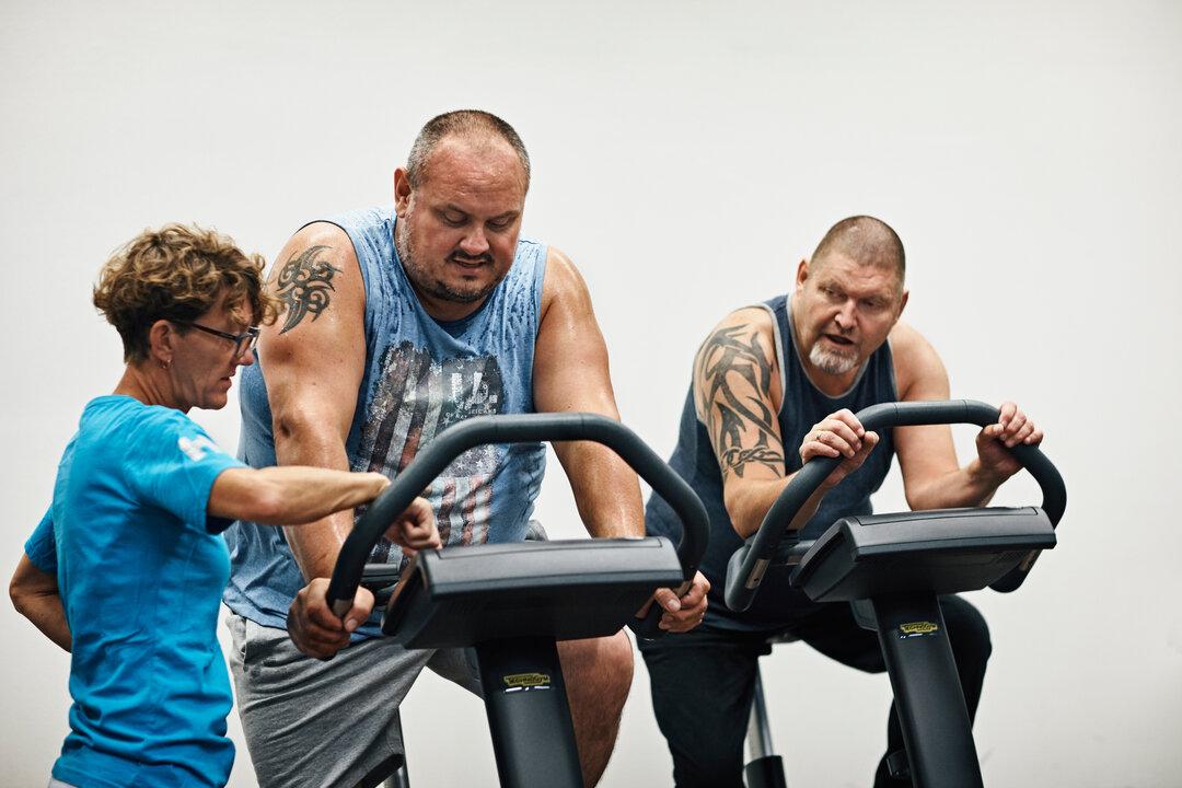 Dekorativt foto at instruktør der vejleder deltagere ved motionscykler