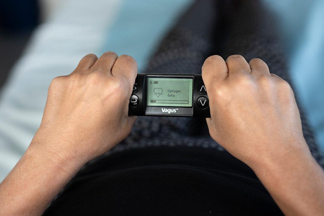Foto vider, hvordan man med begge hænder holder det lille apparat Vagus.